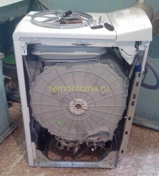 Вид стиральной машины с вертикальной загрузкой при снятой боковой части корпуса